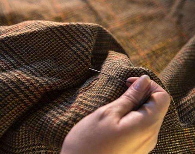 Detail of hand stitching a cloth of tweed